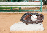 Baseball mitt and ball at first base near dugout