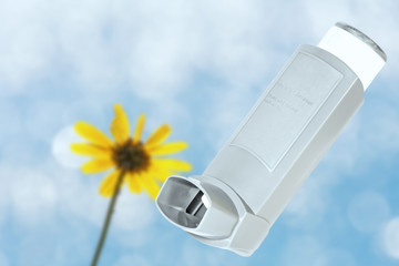 Asthma inhaler sprayer.Blue sky, yellow wildflower background