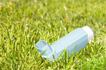 Asthma inhaler sprayer in blades of green grass