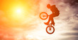 Man doing an jump with a bmx bike against sunshine sky. - 61147297