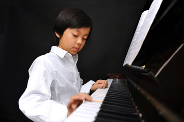 Young boy playing piano (isolated on black background)