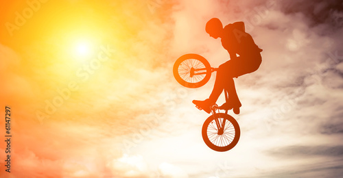 Staande foto Fietsen Man doing an jump with a bmx bike against sunshine sky.