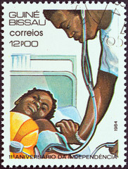 Doctor tending child (Guinea-Bissau 1984)
