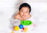 Young boy having bubble bath with toys