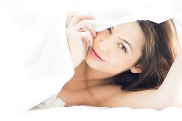 Pretty woman under the bedsheet