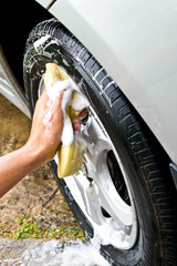 man washing car with a yellow sponge