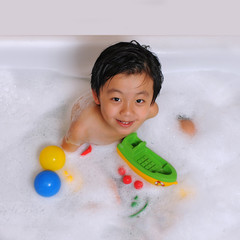 Smiling Asian boy having bubble bath with toys