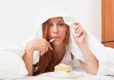 woman eating sweet cake under sheet