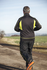 Mature gray haired man while jogging