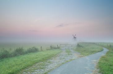 road to Dutch windmill in morning fog