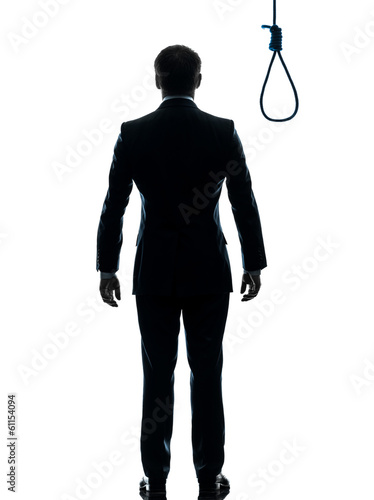 business man standing in front of  hangman noose silhouette rear