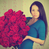 Young brunette woman holding a big bouquet of roses