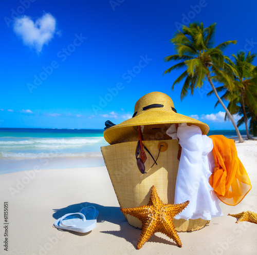 Art Straw hat, bag, sun glasses and flip flops on a tropical bea