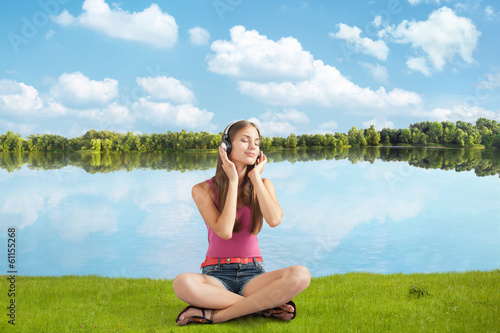 beautiful girl in headphones listens to music near river