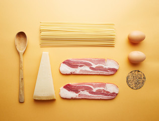 Carbonara ingredients on yellow background