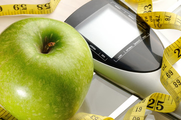 healthy apple, measuring tape and scale