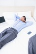 Sleeping businessman lying on his bed