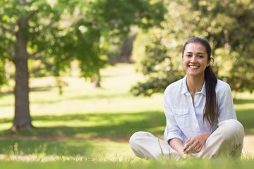 Smiling young woman sitting on grass in park