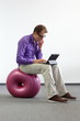 man with tablet on donut ball - bad sitting posture