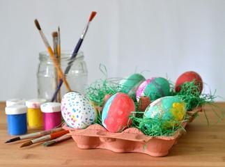 Ostereier in Eierpappe mit Pinsel und Farbe