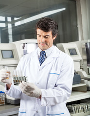 Technician Analyzing Urine Samples In Laboratory