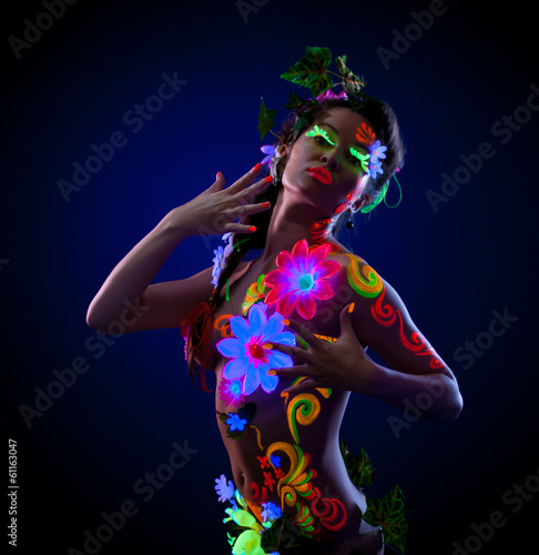 Sexy woman posing with painted flowers on her body