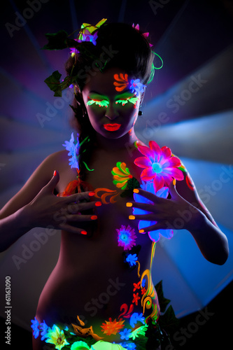 Naked woman with makeup, glowing under UV light