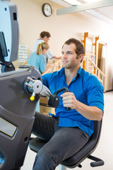 Young Man On Exercise Bike In Hospital