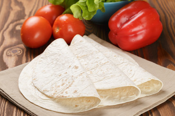 wheat tortillas with vegetables on old wooden table