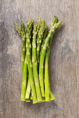 bunch of fresh green asparagus on old wood board