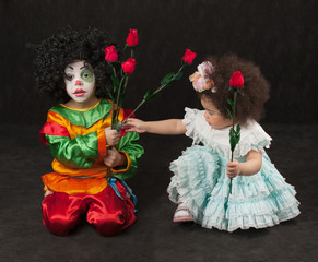 little girl gives flowers to the boy - clown, black