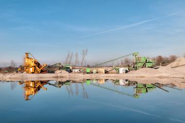 Kiesgrube mit Maschinen und einem Teich