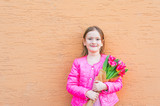 Spring portrait of a cute little girl in a bright pink jacket