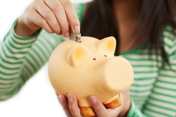 eine Hand füttert Sparschwein mit Geldschein