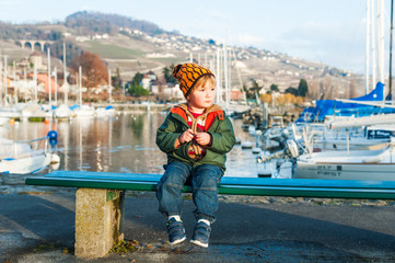 Outdoor portrait of a cute toddler boy sitting on a bench