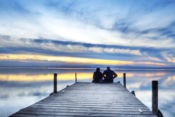 novios en el embarcadero esperando el amanecer
