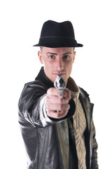 Young man pointing gun at camera, wearing hat and leather jacket