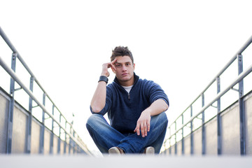 Handsome young man sitting between handrails in walkway