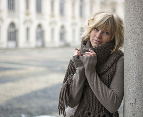 Pretty young blonde woman outdoors, with wool scarf and sweater