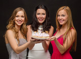 three women holding cake with candles