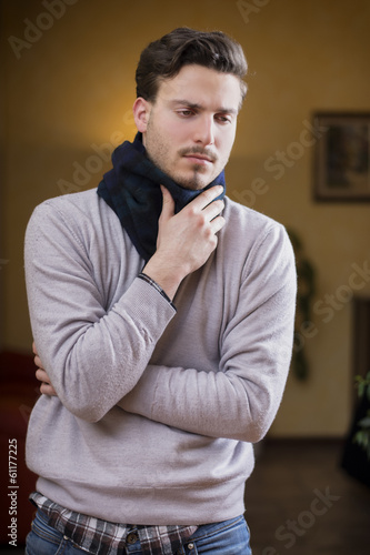 Young man with scarf, holding his neck because of throat ache