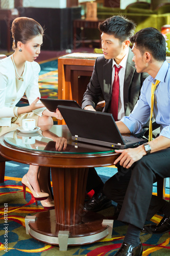 Chinese business people at meeting in hotel lobby