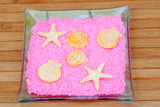 Soaps with shapes of shells and starfish on pink bath salts in a