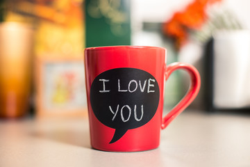 Red ceramic cup with I love you sign made with chalk.
