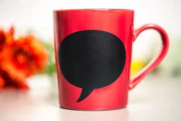 Red ceramic cup with empty chalk board.