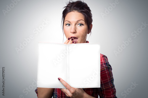 Surprised  young woman holding magazine with empty cover