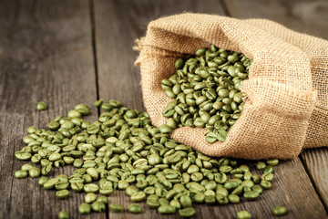 Green coffee beans in bag made from burlap on wooden surface