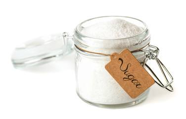 Opened glass jar with sugar. Isolated on white.