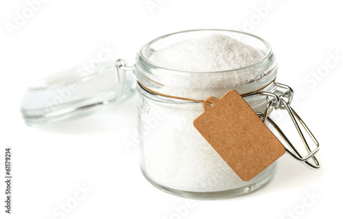 Opened glass jar with paper tag. Isolated on white.