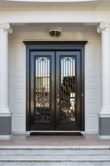 Closed Glossy Black and Glass Front Doors of an Upscale Home